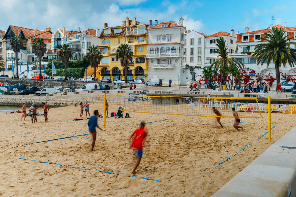 A picture of the city Cascais, Portugal and people playing volleyball.