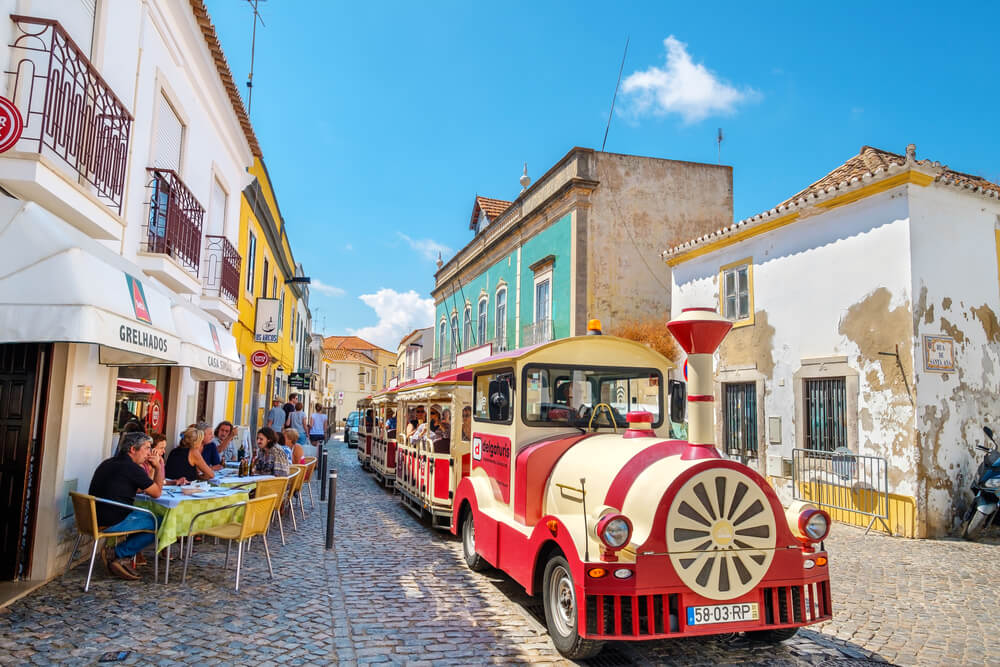 A picture of a train riding through the streets of Tavira, Portugal.