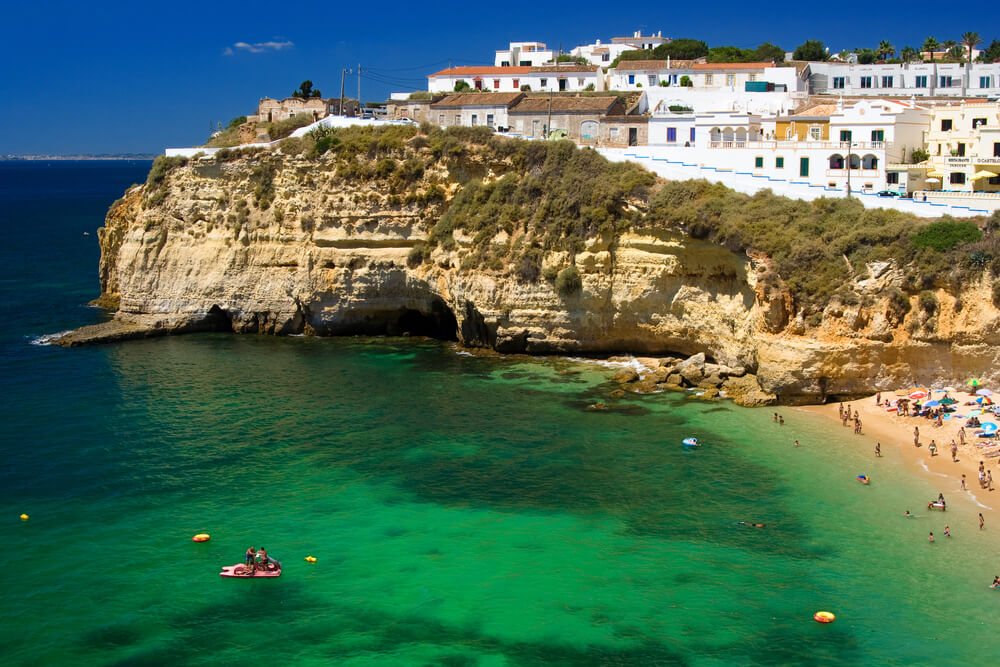 A picture of The Algarve, Portugal with a cliff, sea, and beach in the picture.