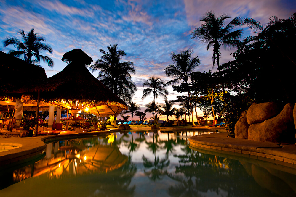 A picture of a resort in Costa Rica. Trees, pool, and pool side bar in the picture.