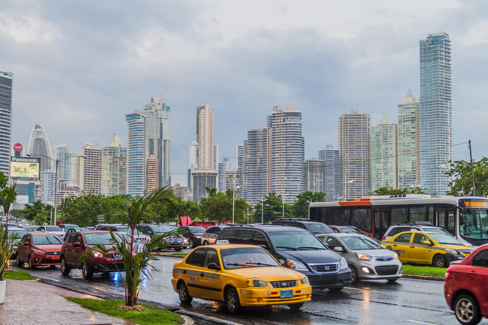 A picture of Panama City, Panama in the background. A busy street filled with cars closer in the picture.