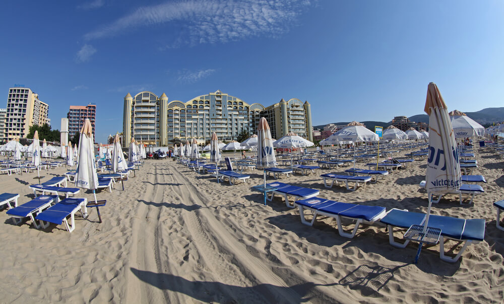 A picture of Sunny Beach, Bulgaria. Beach chairs on sand looking at large residential buildings or hotels.