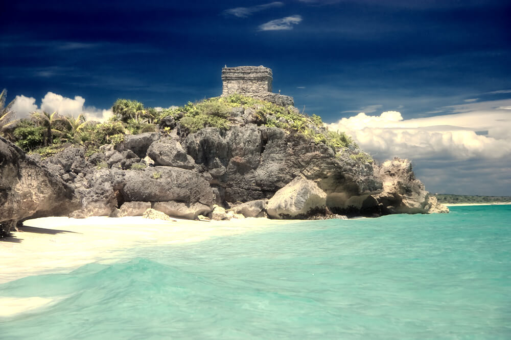 A picture of a cliff, beach, ocean, and clouds in Tulum, Mexico