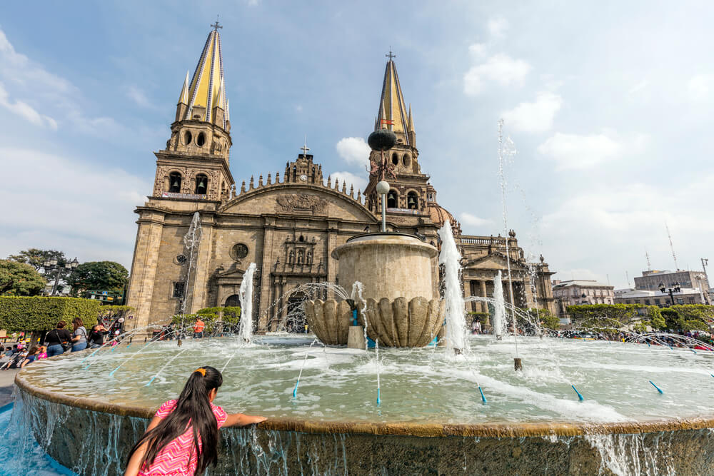 A picture of Guadalajara, Mexico. There's a picture of a large fountain in front of what appears to be a large church. There are people around the fountain.