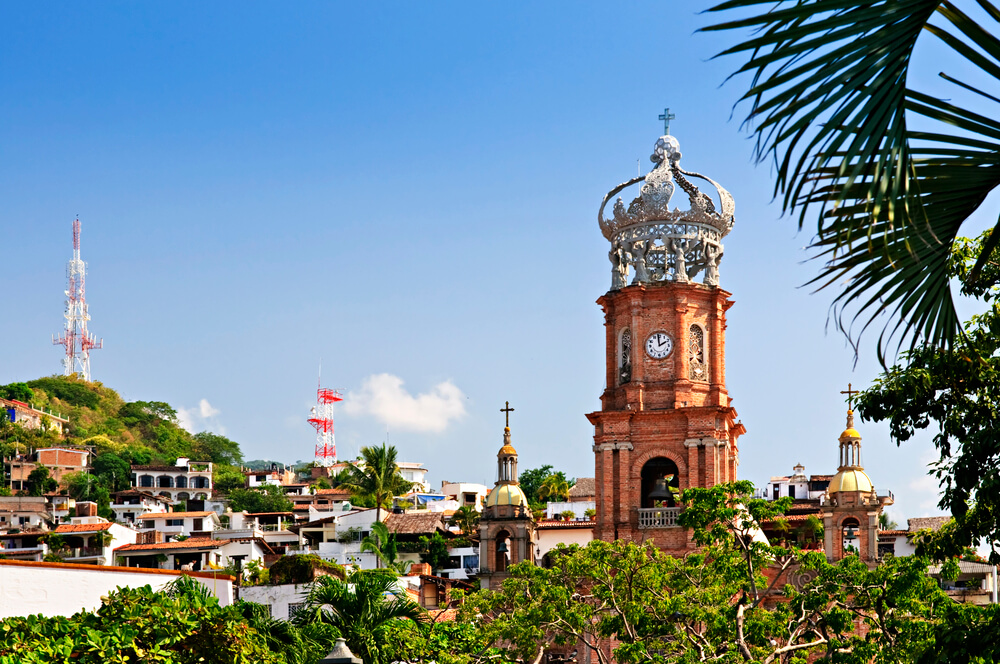 An image of houses and buildings in Puerto Vallarta, Mexico. Churches and some trees.