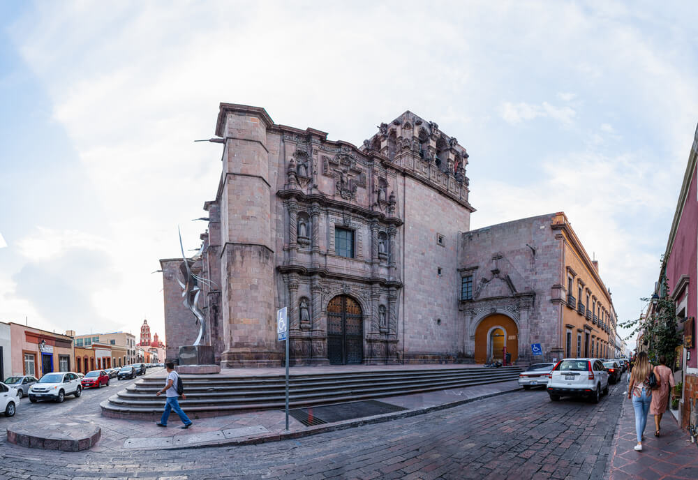 An image of the city streets of Santiago de Querétaro, Mexico. People and cars moving about and a large brick building on a corner.