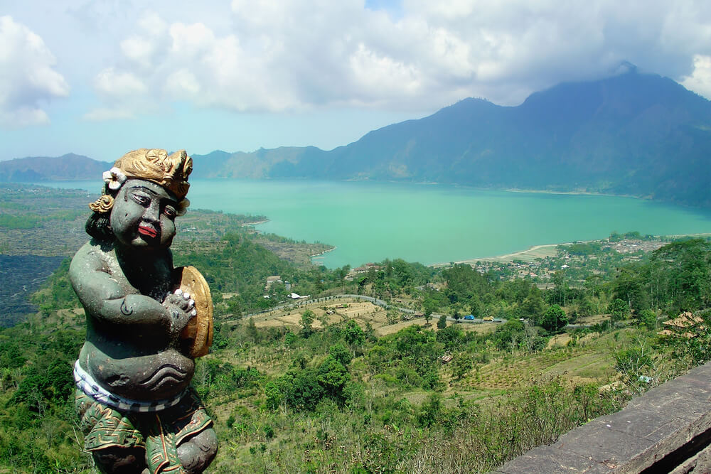 A picture from an elevated view overlooking a bay and a volcano in Indonesia A cultural statue close in view.