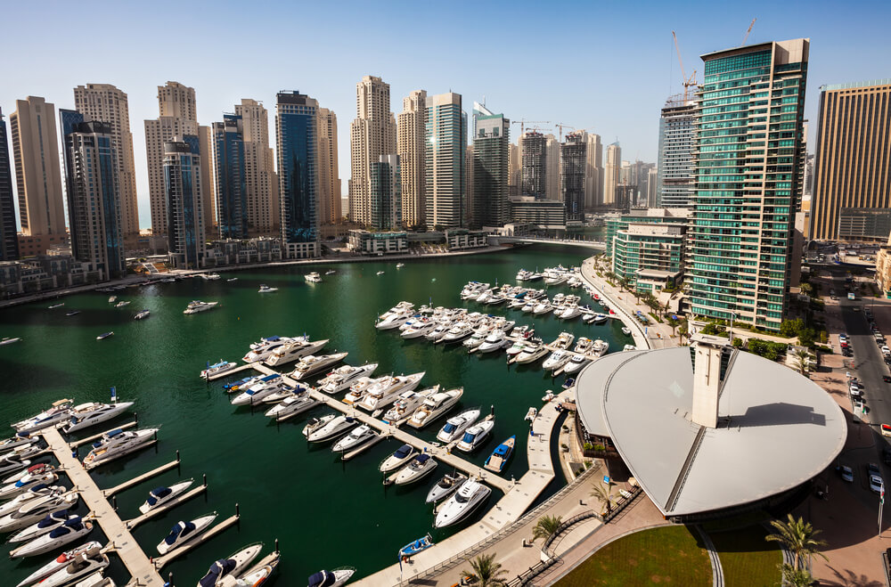 A picture of a marina in Dubai. Lots of boats docked in the middle of the city. Tall, high rise buildings all around.