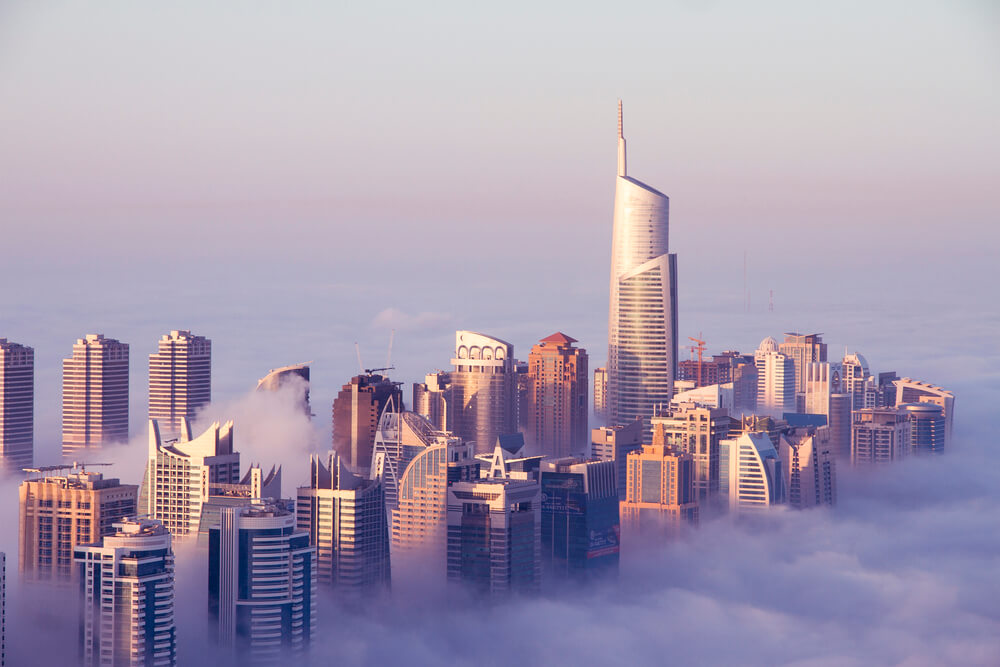 An aerial view of Dubai in the morning. Fog covering the base of the buildings and you can see the top of the buildings.