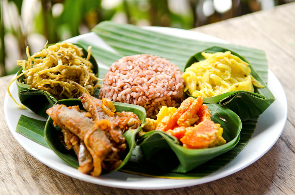 A picture of Indonesian cuisine on a plate sitting on a wooden surface. 5 different foods.