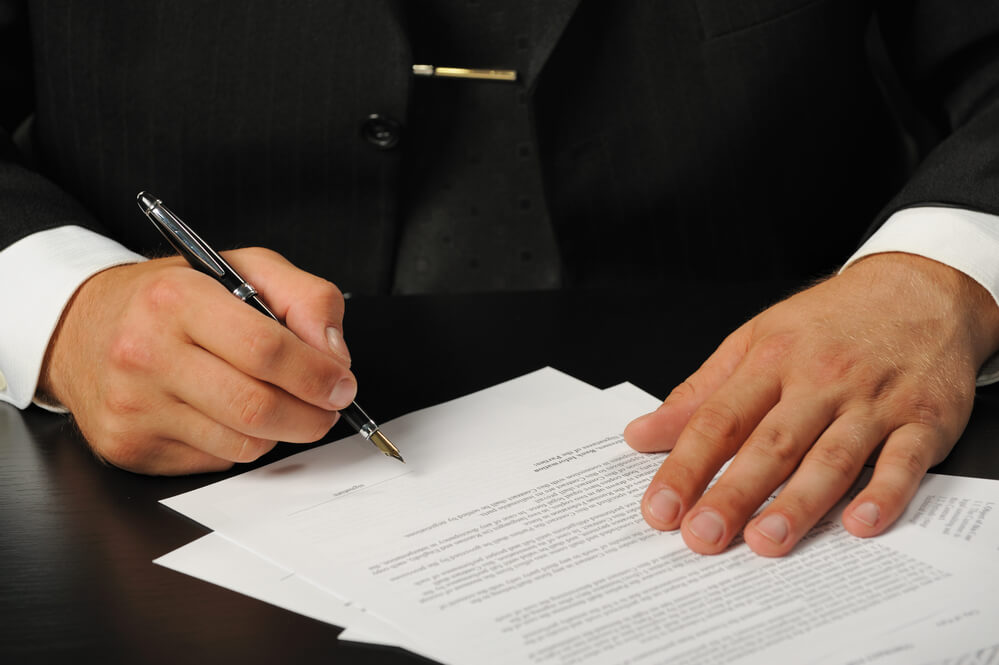 A picture of a business person signing a document used to depict someone signing their Fideicomiso documents.