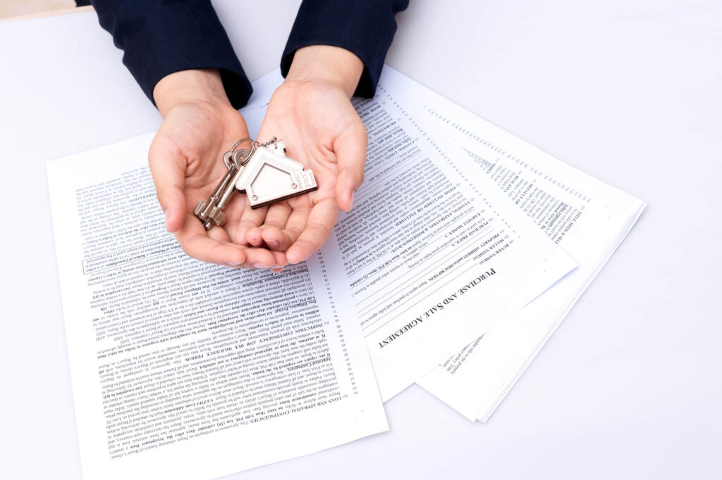 A Person Holds A Gold Keychain With A Home And Key Above A Stack Of Legal Papers