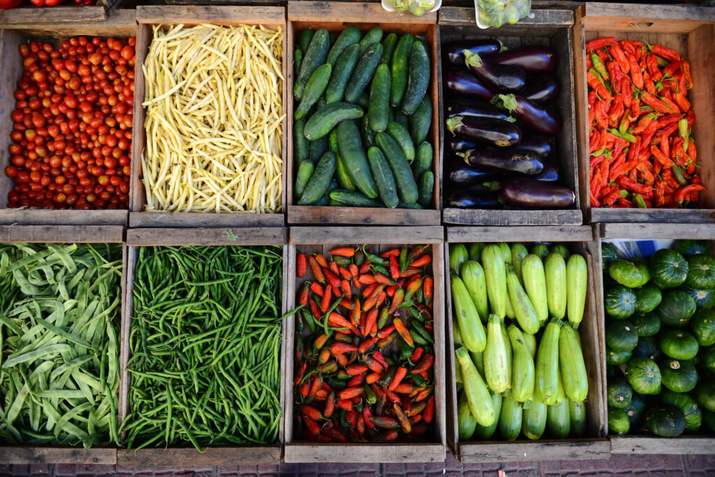 A collection of fresh vegetables from a market in Montevideo Uruguay, including fresh green beans, bright red chilli, tomatoes, pumpkin, snow peas, cucumber, and eggplant