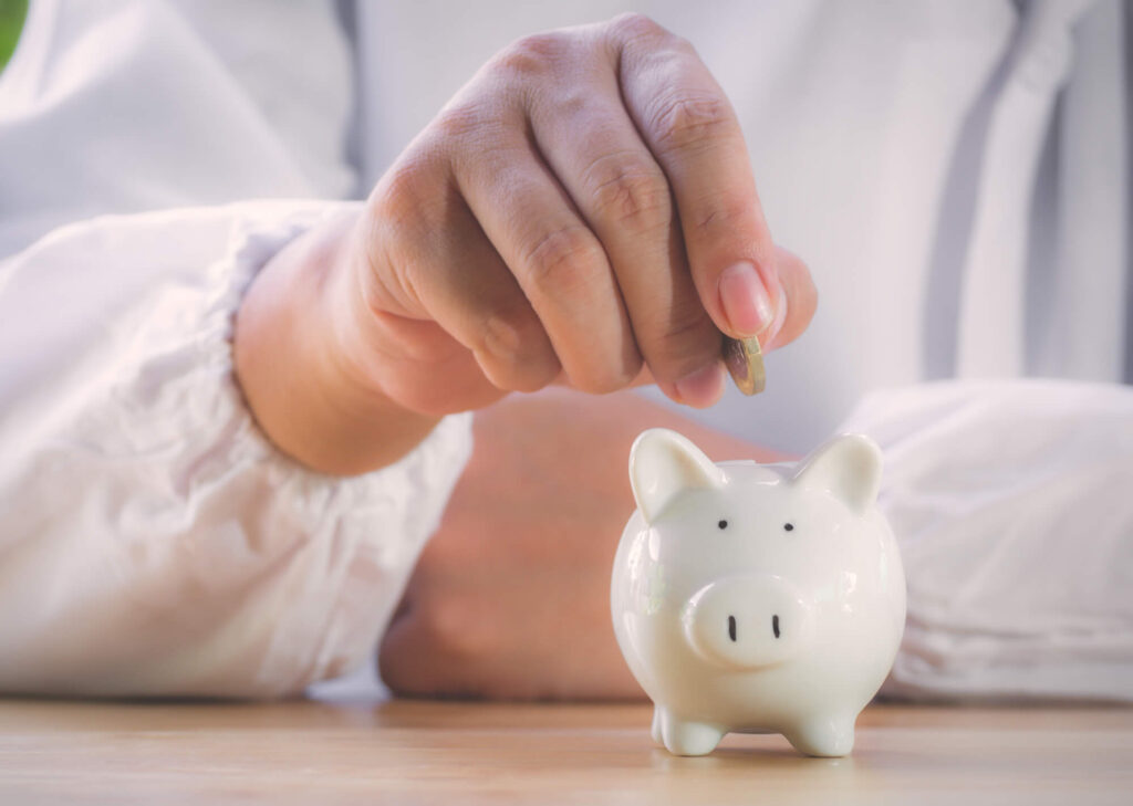 A photo of an older person wearing a white shirt putting a coin into a small white piggy bank