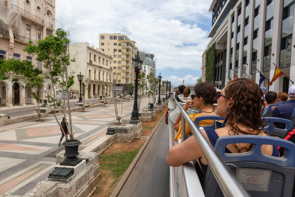 A photo showing a group of tourists sitting on a roofless bus as it drives through the CBD of Havana Cuba