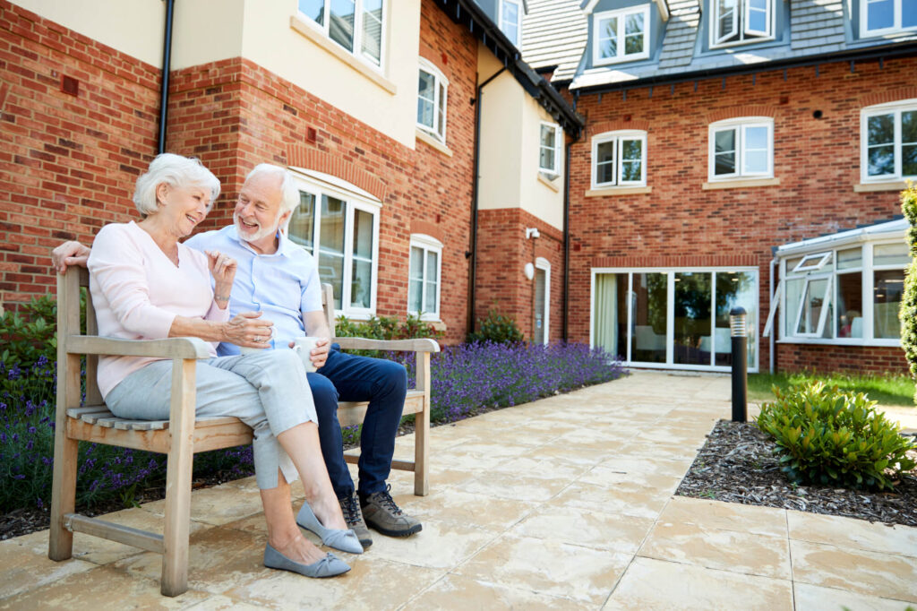 A picture of an older couple sitting on a bench outside of an aged care facility