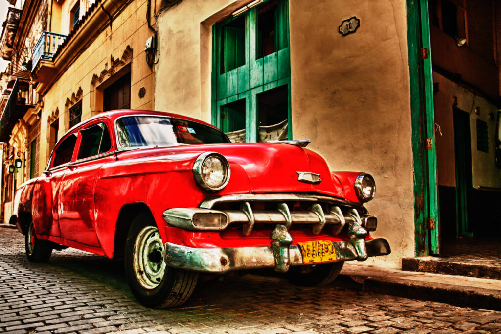 A red vintage American car from the 1940s is parked on a paved street in Havana, Cuba. It is in front of an old apartment building with green doors