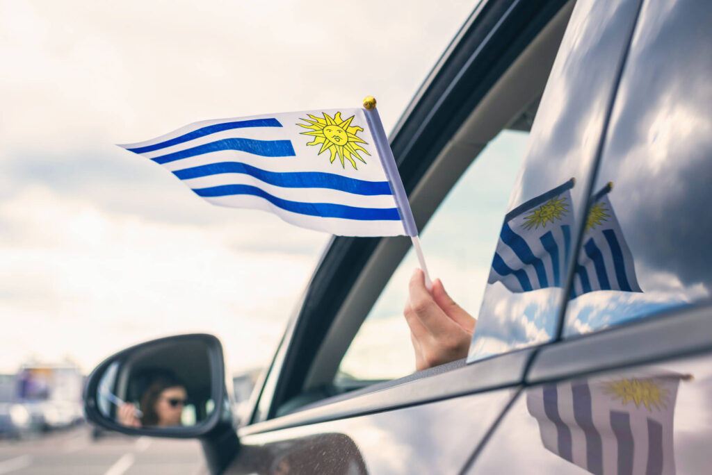 A young woman driving a car on a road in Uruguay while waving a Uruguayan flag out the window