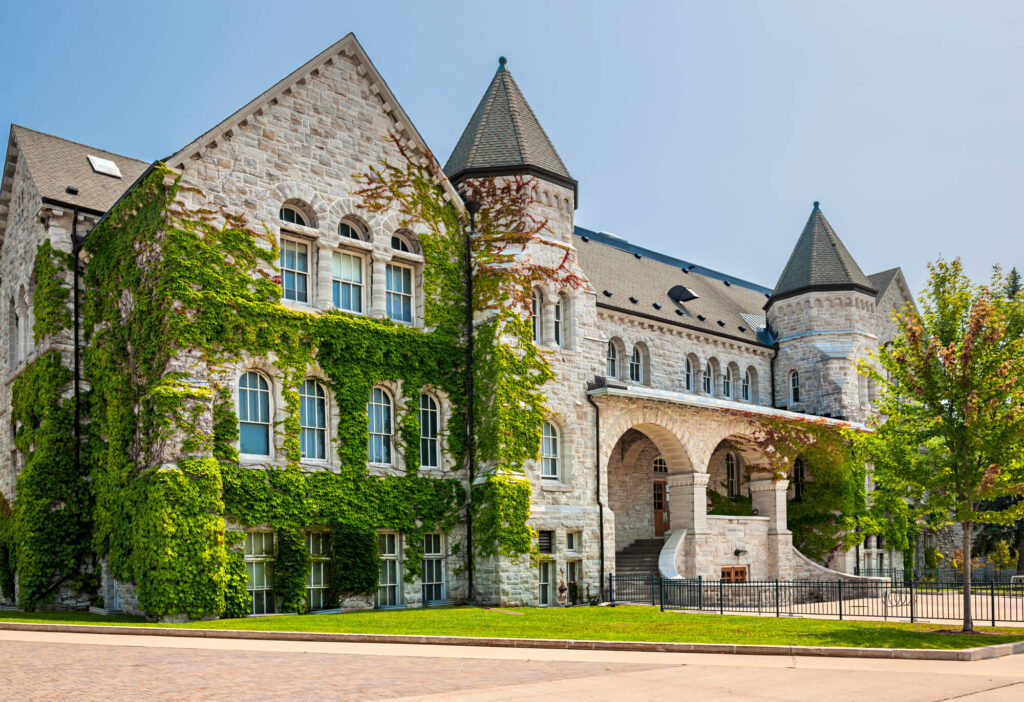 An image of Queen's University Ontario Hall in Canada. It shows a large sandstone in a gothic architectural style with vines growing on it