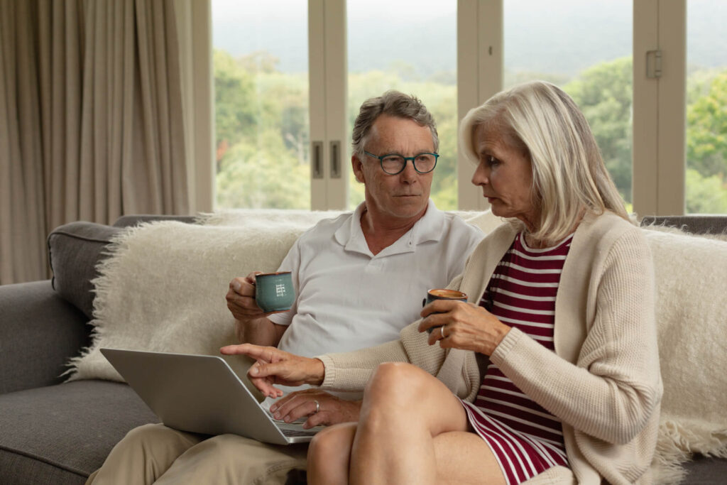 An image of an older couple sitting on a couch drinking coffee as they look at a laptop