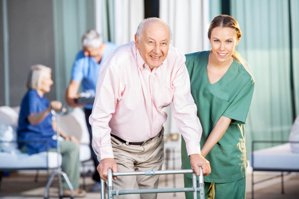An image of an older gentleman in a nursing home using a zimmer frame. He is being assisted by a nurse