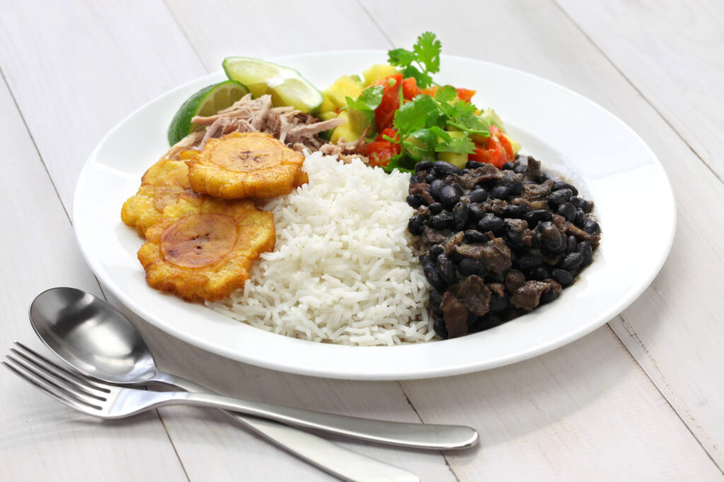 An image of traditional Cuban food, including rice, black beans, fried plantains, shredded pork, limes, cilantro, and salad