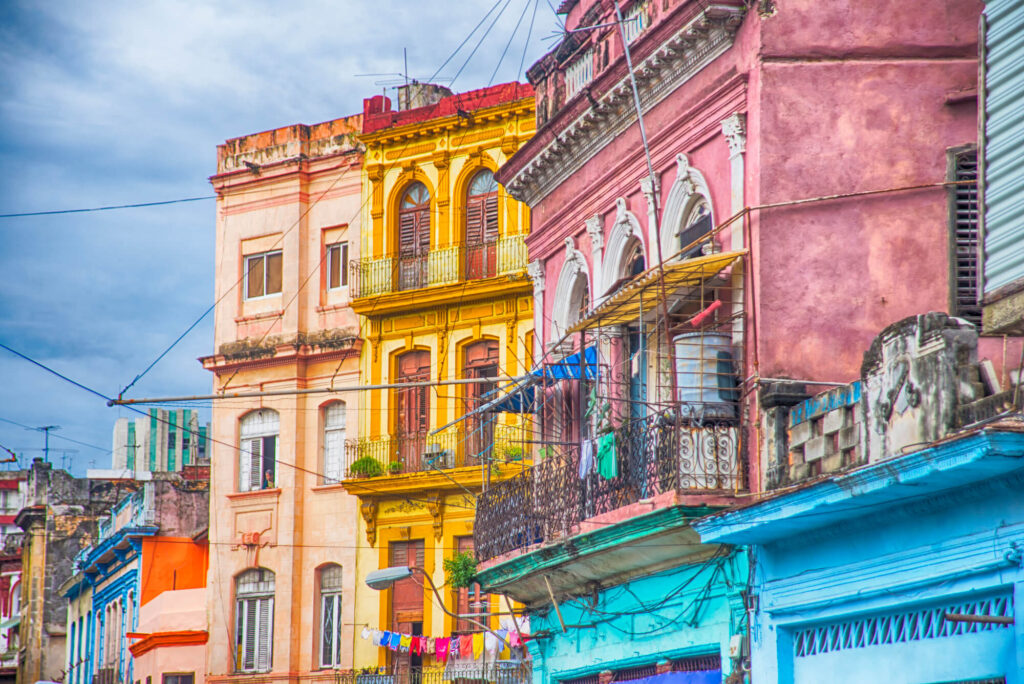 An image showing a group of colorful buildings in Havana Cuba including yellow, pink, orange, andblue buildings with balconies and awnings