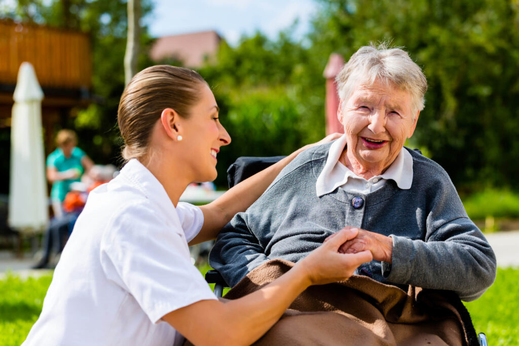 An older lady sitting in a wheelchair is being assisted by a female nurse. They are sitting outside on a sunny day on a green lawn. There is an umbrella, trees, and buildings in the background