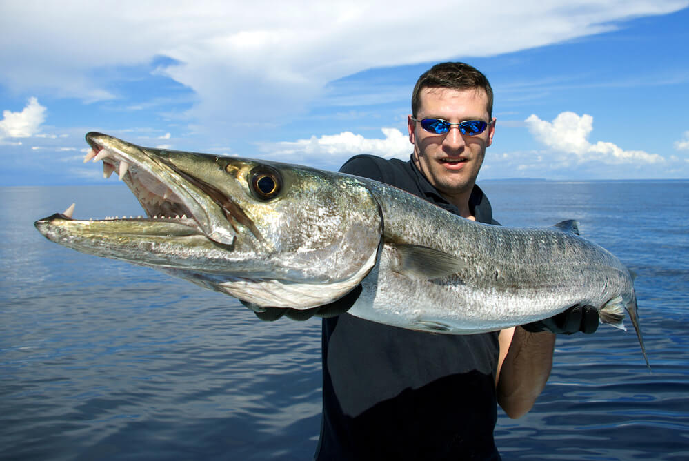 A picture of a man holding a barracuda that he caught while fishing.