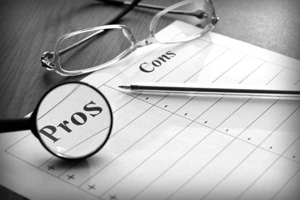 This image shows a pair of reading glasses and a pen laying on top of a piece of paper labeled pros and cons. A magnifying glass highlights the pros