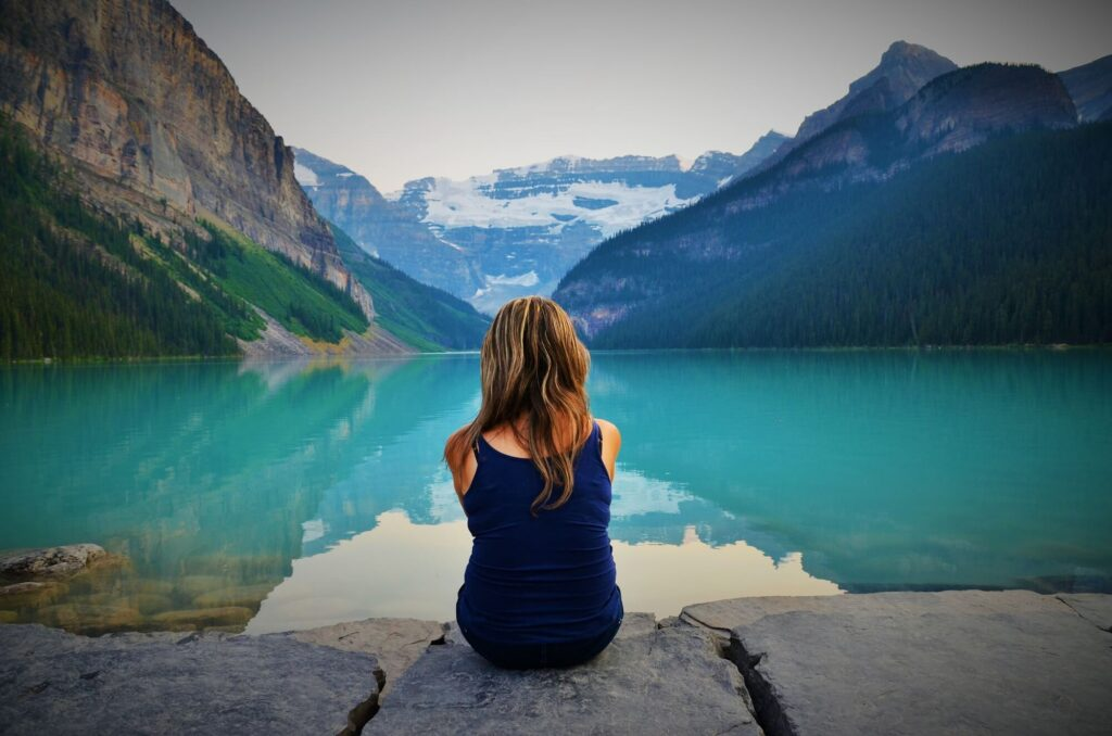 This image shows a young blonde haired woman sitting on a stone wall at Lake Louise, Canada