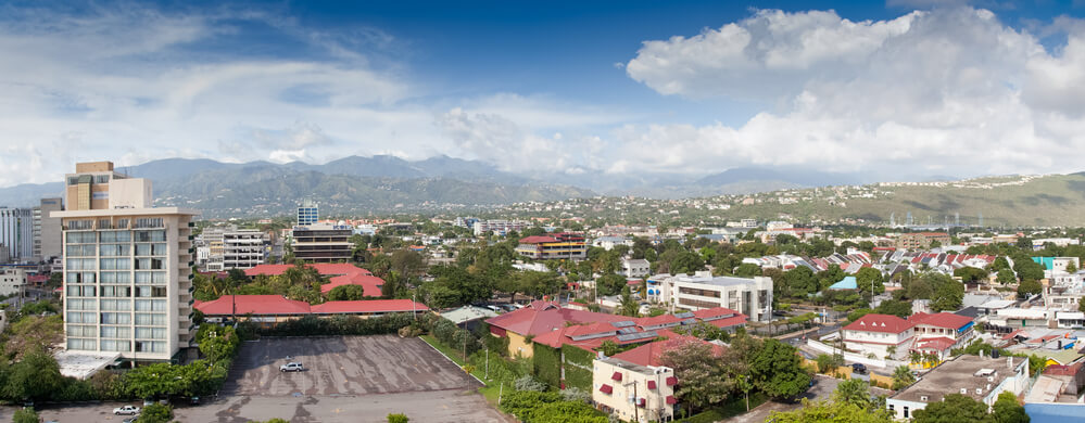 A picture of houses and condos in Jamaica. There's also several Jamaican businesses and cars driving the city streets. Clouds above the city and mountains in the background.