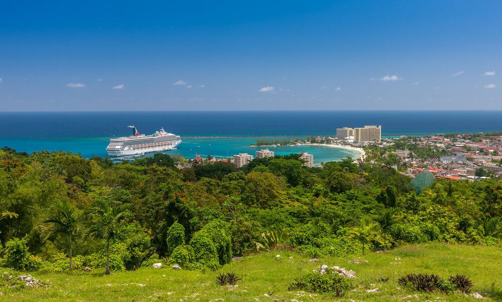 A picture of a bay in Jamaica from the top of a hill. You can see a cruise ship, hotel, and other buildings as well as lots of trees.