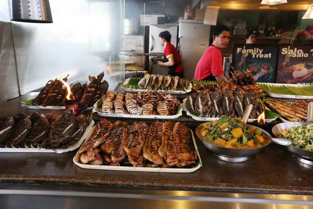 A picture of two chefs cooking food, primarily meat in Manila, Philippines.