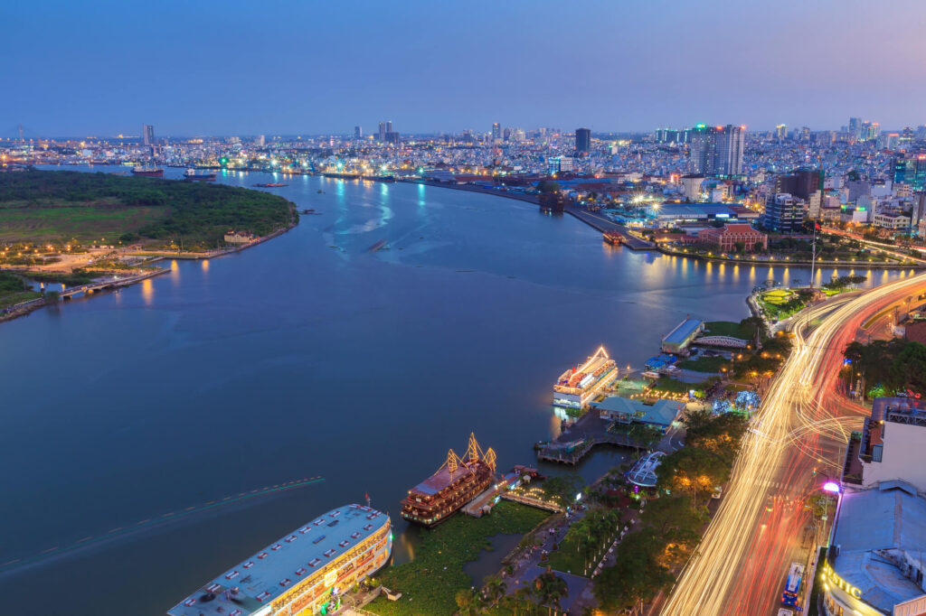A night time photo of Ho Chi Minh City, featuring a large river and cityscape. There are multiple ferries moored at the riverbank