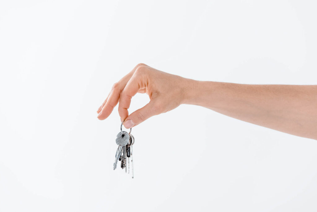 A photo of a person's hand holding a set of house keys, symbolizing property ownership