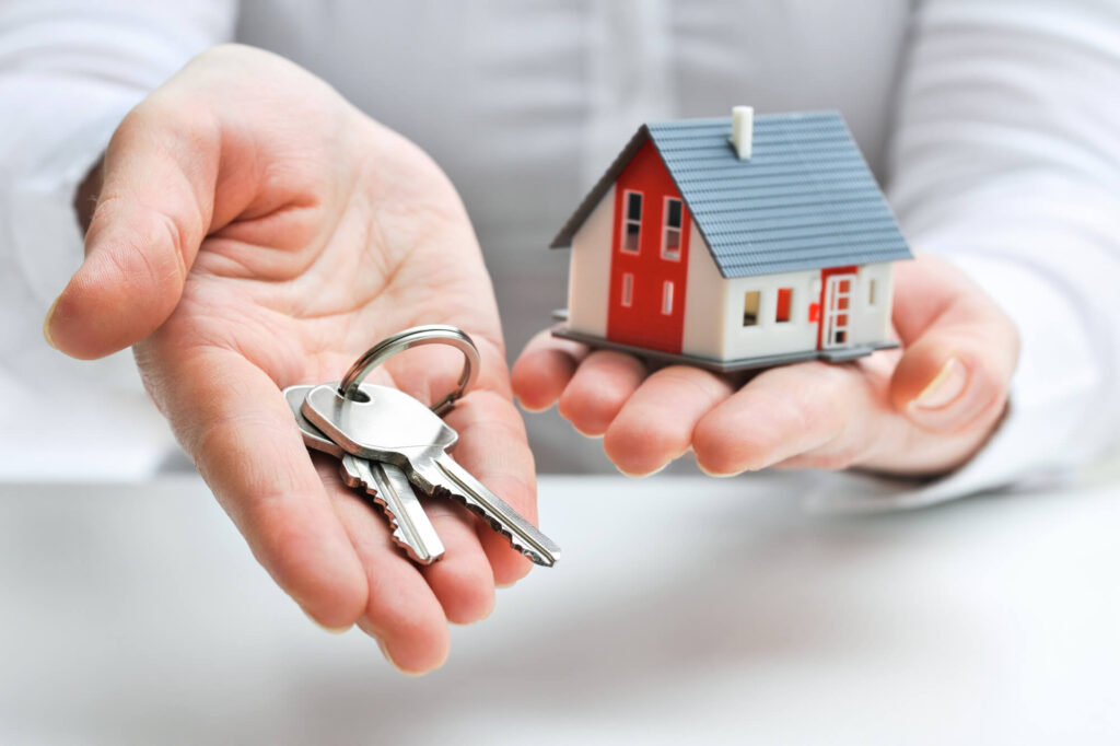 A photo of a person's hands holding house keys on one hand and a model house in the other