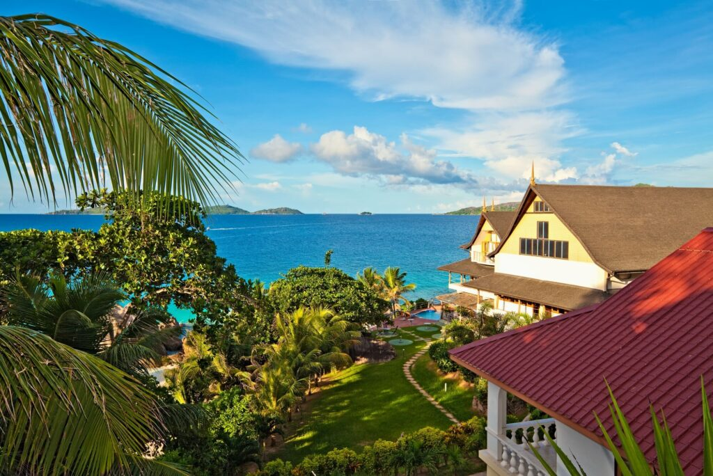 A photo of houses in the Seychelles featuring two large homes,  several palm trees, a blue sky and light blue ocean water