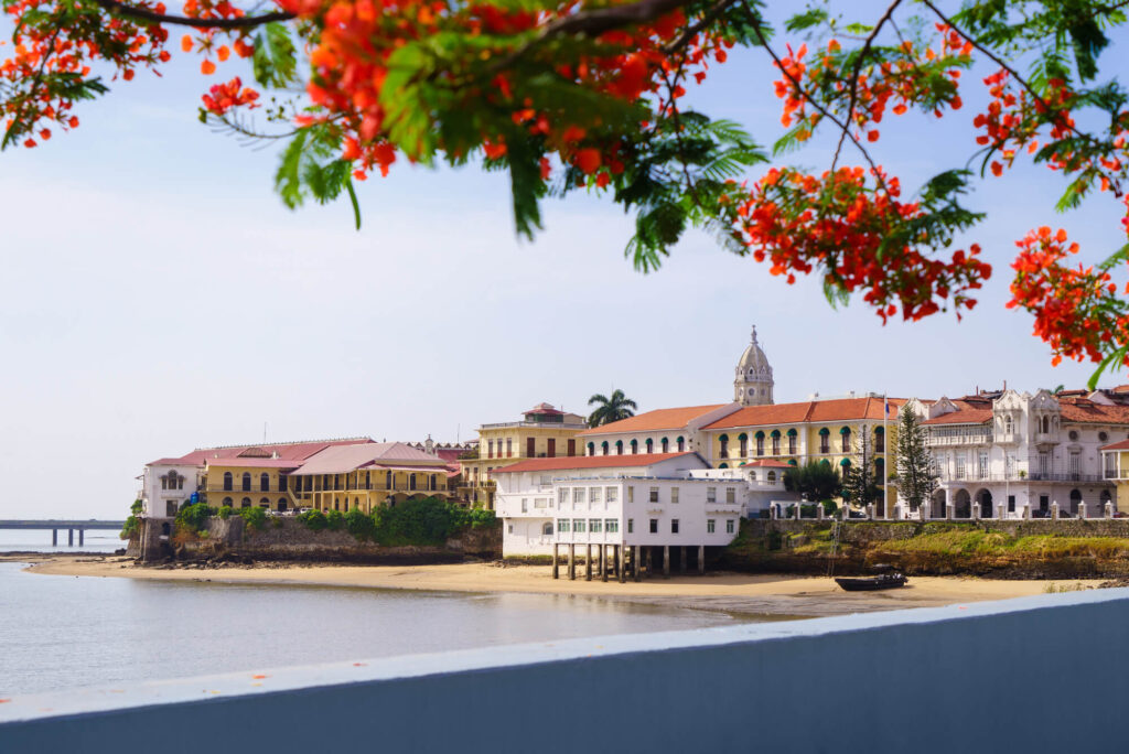A photo of old casco viejo antiguo in Panama City. It shows a large property on a wide calm bay, with an orange roof and white walls. One building is on stills and sits on the beach