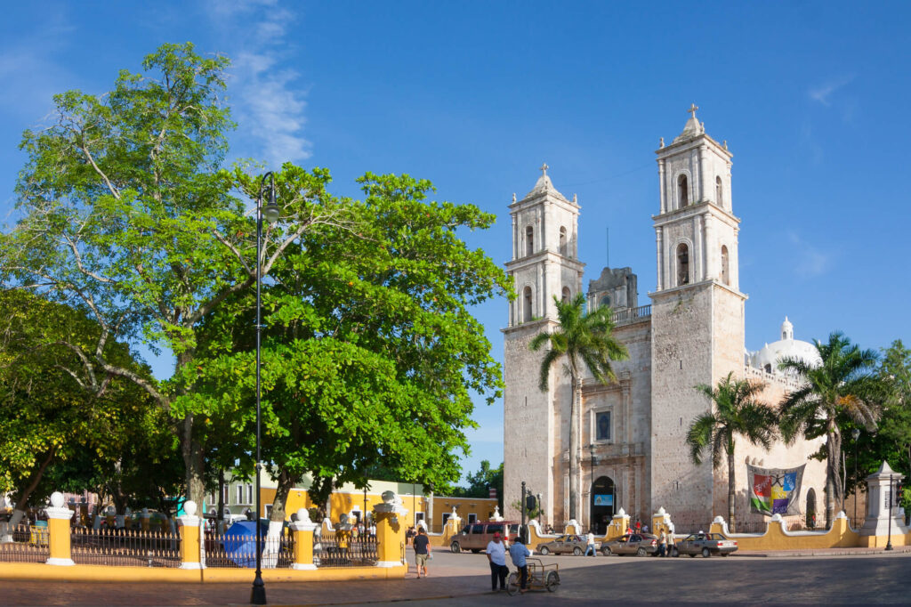 A photo of the Cathedral of San Ildefonso in Merida, the capital of Yucatan Mexico. It shows a large church opposite a park with trees