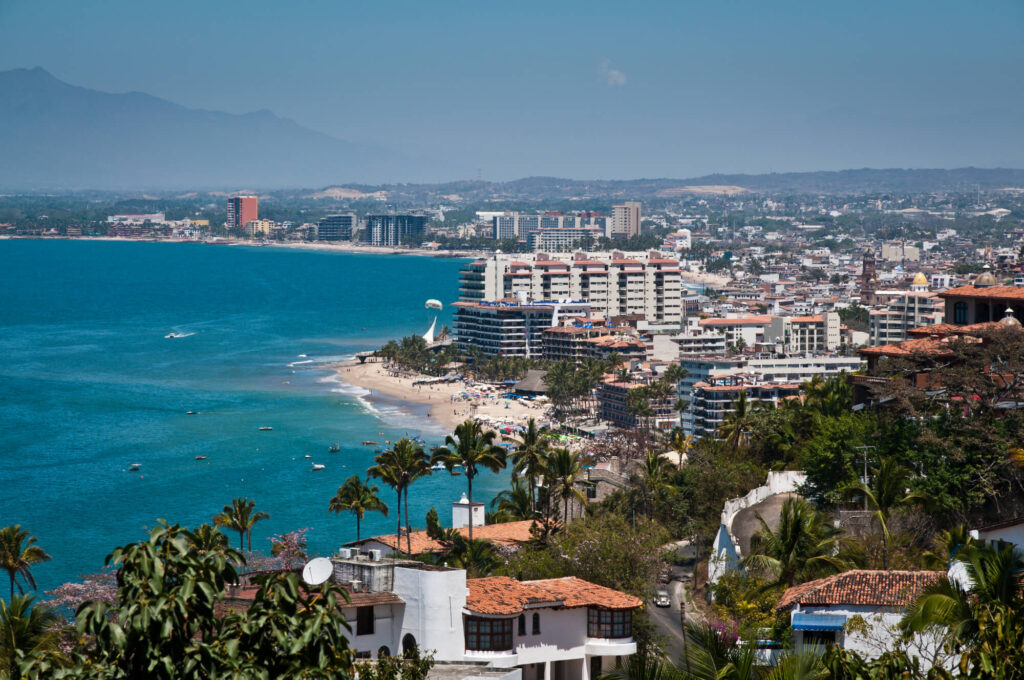 A photo of the coastline in Puerto Vallarta, Mexico, featuring several beaches, large hotels, and palm trees