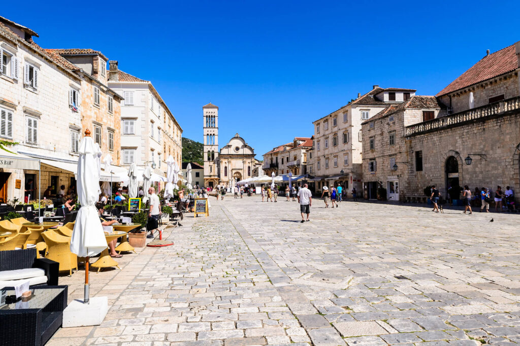 A photo of the main square of the old town of Hvar on Hvar island in Croatia. Dozens of people are walking along a stone paved street lined with cafes and restaurants