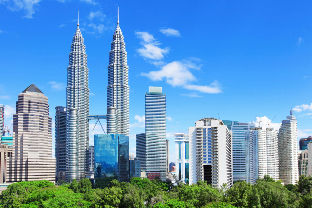 A photo of the skyline in Malaysia. It shows several huge, modern sky scrapers. A row of trees is in the foreground of the image