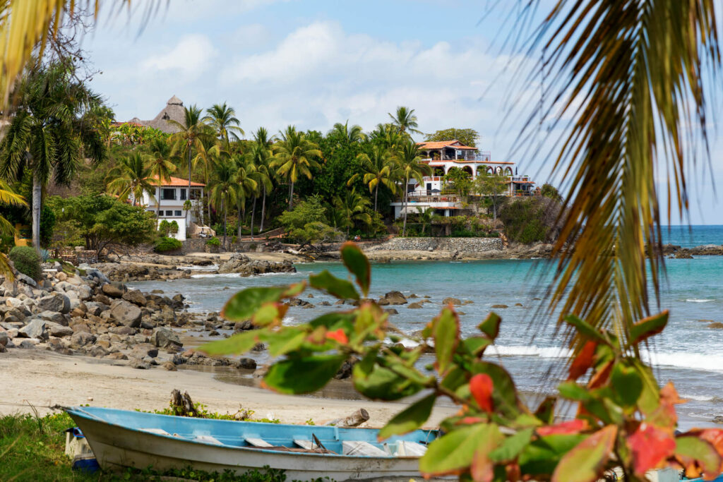 A photo of the small surfy village of Sayulita, Nayarit, Mexico, showing a large sweeping cove with several small boats and a large home