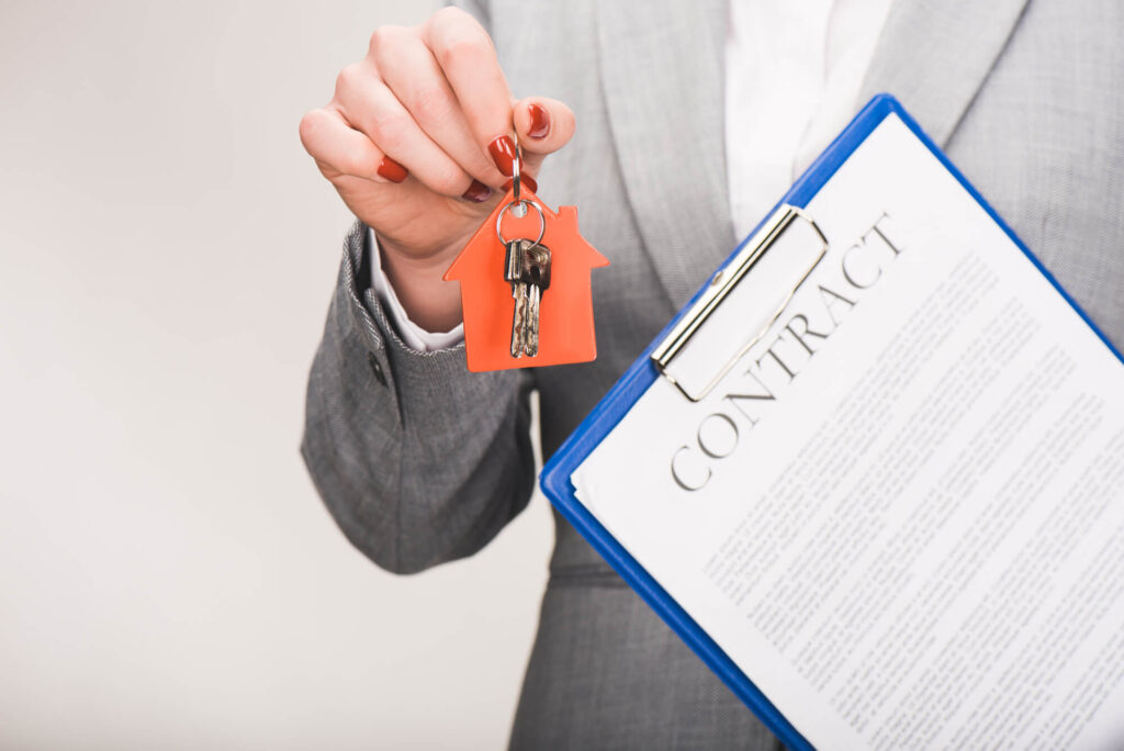A photograp of a person in a gray suit holding a set of house keys in their hand and a clipboard with a real estate contract under one arm