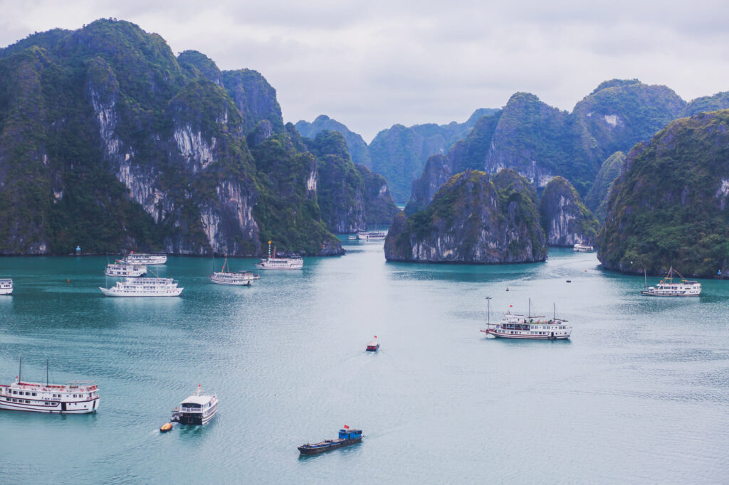 A photograph of Halong Bay, Vietnam, a UNESCO World Heritage Site. It shows a series of steep rocks in a bay. A number of boats are floating in the area