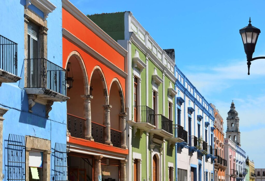 A photograph of a street in Campeche City in Mexico, showing a row of colorful buildings and a blue sly