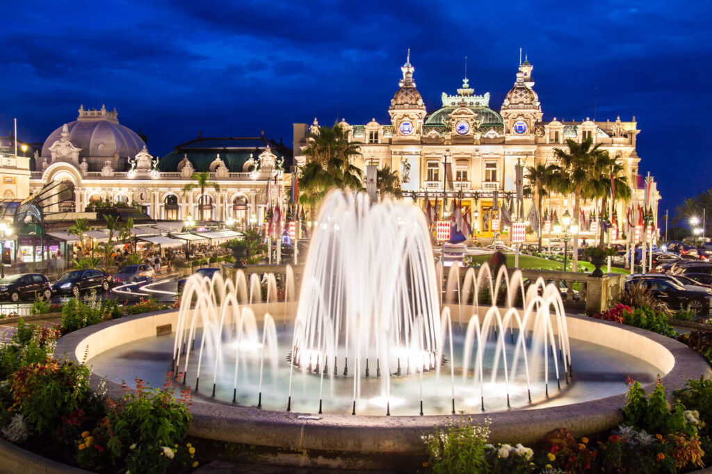 A photograph of the Monte Carlo casino. It shows a large waterfall in the foreground and the casino in the background