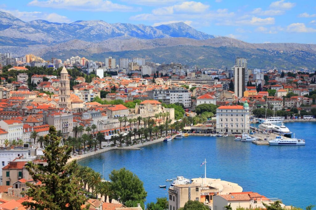A photograph of the city of Split, Croatia. It shows a port, dozens of old buildings, and hills in the distance