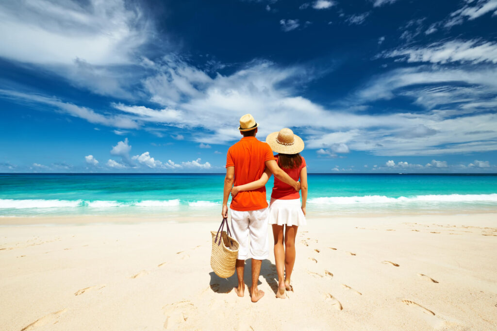 A photograph showing a couple standing on a white sandy beach looking at a calm blue ocean in the Seychelles